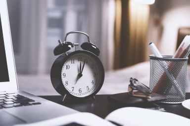 black twin bell alarm desk clock on table